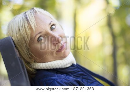 Plain Forty Year Old Woman On A Park Bench