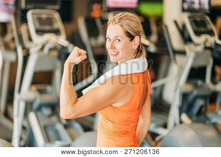 Happy And Healthy Woman In Sport Gym, Holding White Towel, Looking Back Over The Shoulder