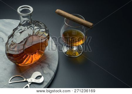 A Brandy Decanter And A Stainless Steel Cigar Cutter On The Marble Tray, A Cuban Cigar With A Snifte