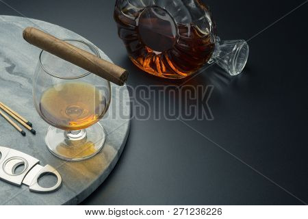 A Cuban Cigar On A Snifter Glass Of Brandy And A Stainless Steel Cigar Cutter With Matches On The Ma