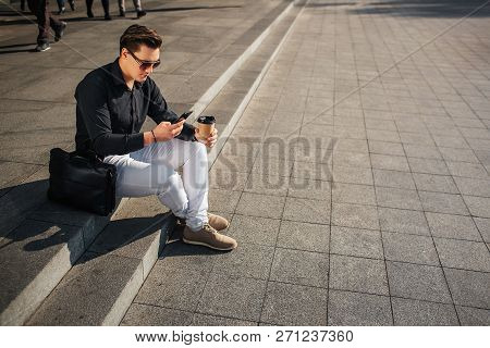 Well-dressed Young Man Sit On Steps Outside And Look At Phone. He Hold Cup Of Coffee. Leather Bag Is