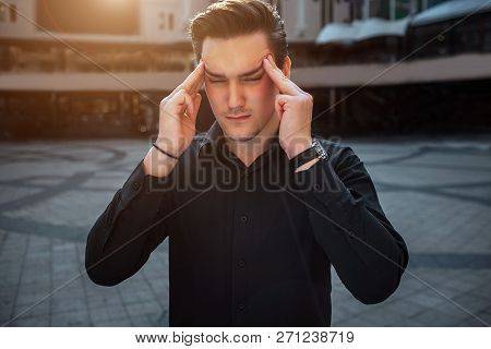 Young Man Stand Outside And Hold Fingers On Plummet. He Keeps Eyes Closed. It Is Sunny Outside.