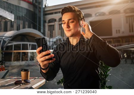 Young Man Hold Phone In Hand. He Is Outside At Table. Guy Listen To Music. It Is Sunny Outside.