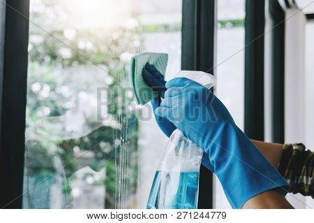 Husband Housekeeping And Cleaning Concept, Happy Young Man Wiping Dust Using A Spray And A Duster Wh