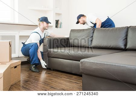 Delivery Man Move Furniture Carry Sofa For Moving To An Apartment. Professional Worker Of Transporta