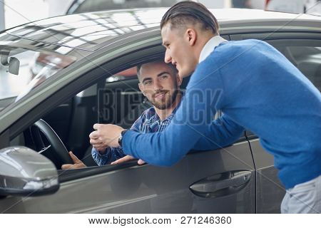 Brunette Client With Beard Sitting In Grey Car And Holding His Hand On Steering Wheel. Menager In Bl
