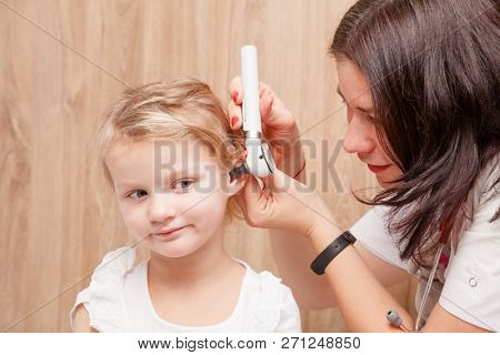 Female pediatrician examines little girl's ear. Doctor using a otoscope or auriscope to check ear canal and eardrum membrane. Child ENT check concept