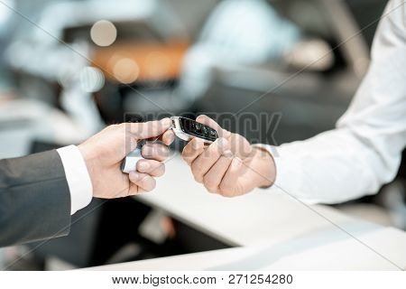 Salesperson Giving A Keychain From A New Car To A Client At The Stand In The Car Showroom, Close-up