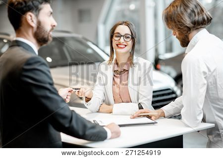Young Business Couple Signing Some Documents At The Table With Salesperson Or Manager Buying Or Rent