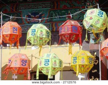 OLYMPUS DIGITAL CAMERA Daegu South Korea Korean lanterns in front of a temple on the eve of Buddha's birthday orange green yellow red shapes Korean characters are written on each lantern a holy celebration of one so revered in a typically traditional poster