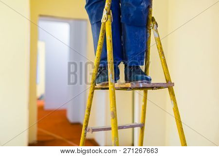 Legs Of Worker With Blue Workwear And Black Shoes On The Wooden Stepladder. Worker Makes Plasterboar