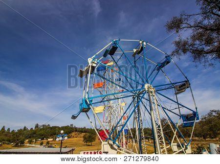 Old Colorful Ferris Wheel In Disrepair At Storage Field