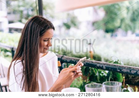 Attractive Woman Is Sitting In A Summer Street Cafe With A Phone.