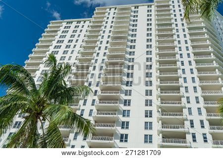 High-rise Condominium In Miami, Florida With Palm Trees In Foreground.