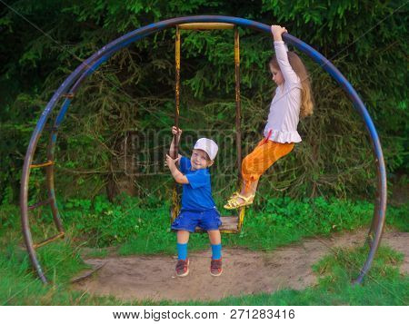 Little Children, A Girl And A Boy, Brother And Sister, Play On An Old Vintage Swing. The Boy Is Swin