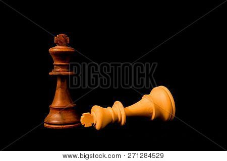 White King Surreder To Black King At The End Of The Game. Two Strandard Chess Wooden Pieces On Black