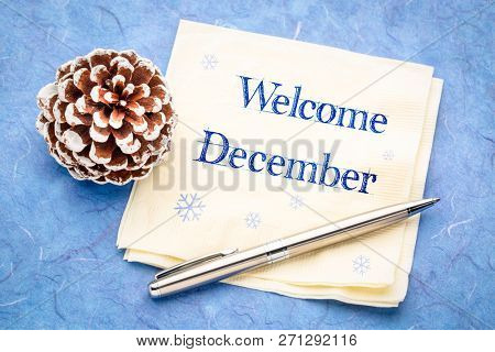 Welcome December -  handwriting on a napkin with a frosty pine cone