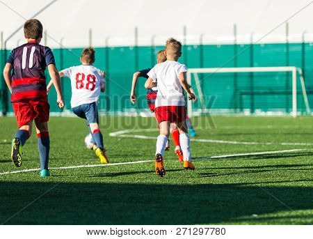 Young Footballer In Red And Blue Sportswear Running, Dribble And Playing Football Ball. Junior Footb