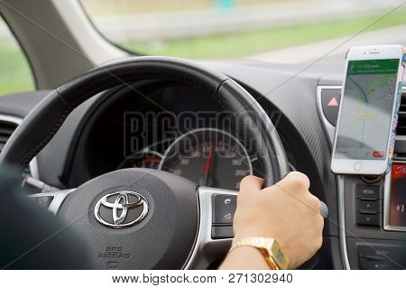 Hands Of Man With A Steering Wheel, Driving A Car On A Smartphone Navigator. Photo Of A Man Driving