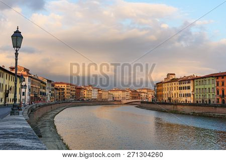 View on embankment of Arno river and bridge Ponte Di Mezzo at sunset in Pisa, Italy poster