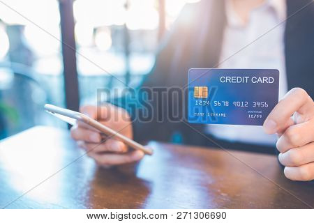 Business Woman Hand Holds A Blue Credit Card And Use A Cell Phone In The Office.