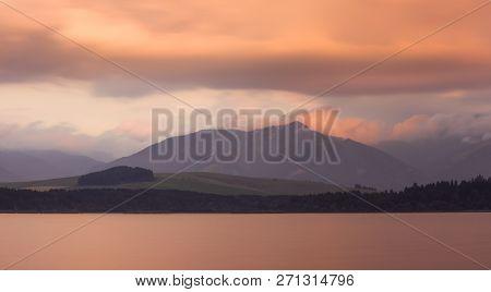 Long Exposure Shot Of Liptovska Mara Lake, Low Tatras Mountains And Cloudy Sky At Sunset.
