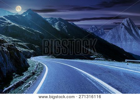 Road In Mountains With Rocky Ridge In The Distance At Night In Full Moon Light. Composite Image. Tra
