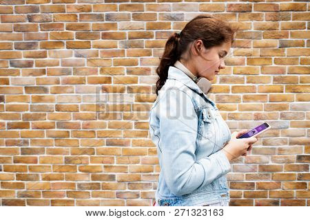 Teen girl texting on her phone by a brick wall