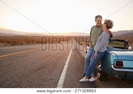 Senior couple on road trip standing by car, full length