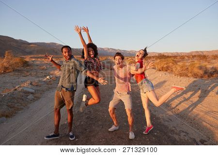 Young adult friends have fun striking poses in the desert