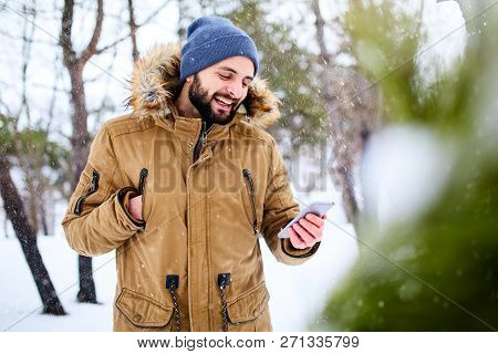 Smiling Bearded Man Wears Warm Winter Clothes And Using Smartphone With Fast Internet Data Connectio