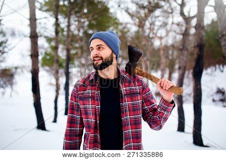 Bearded Hipster Man In A Winter Snowy Forest With Axe On A Shoulder. Woodman Standing In The Forest.