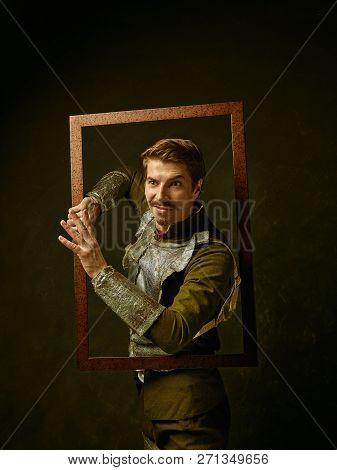 Medieval Knight On Dark Studio Background. Portrait In Low Key Of Brutal Man In Tradishional Retro C