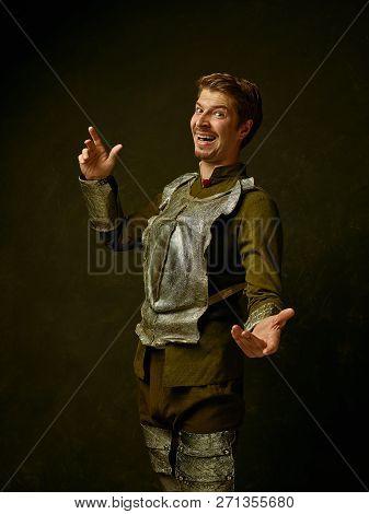 Medieval Happy Knight On Dark Studio Background. Portrait In Low Key Of Brutal Man In Tradishional R