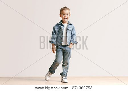 The Portrait Of Cute Little Kid Boy In Stylish Jeans Clothes Looking At Camera Against White Studio