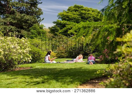 Edinburgh, Scotland - May 19: People Lying On The Grass In Royal Botanic Garden On May 19, 2018 In E