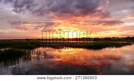 Beautiful Sunset Over Marsh Grass And Coastal Ocean Waters At High Tide With Forest In The Backgroun
