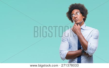 Afro american business man wearing glasses over isolated background with hand on chin thinking about question, pensive expression. Smiling with thoughtful face. Doubt concept.
