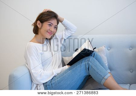 Cheerful Asian Girl Making Her To Do List. Beautiful Young Woman Resting On Couch With Her Organizer