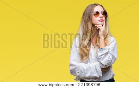 Young beautiful blonde woman wearing sunglasses over isolated background with hand on chin thinking about question, pensive expression. Smiling with thoughtful face. Doubt concept.