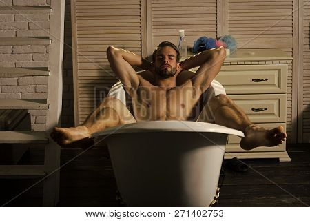 Bodycare, wellness, pleasure, relax. Man with muscular legs, chest, arms, biceps, triceps in bath. Bath, bathing, shower, spa Hygiene grooming health Sexy macho relax naked in bathtub in bathroom poster