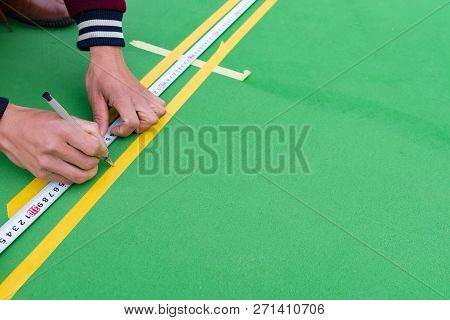 Workers Taping And Marking The Sideline On The Floor For An Outdoor Stadium