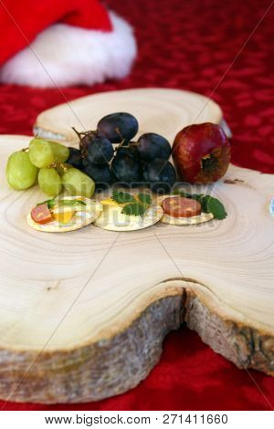 Room for Text Overlay. Appetizers on a tree stump cutting board for a Christmas. Appetizers consisting of cheeses, fruits, sausages, crackers and fresh herbs. Wooden Tree Stump Cutting board.
