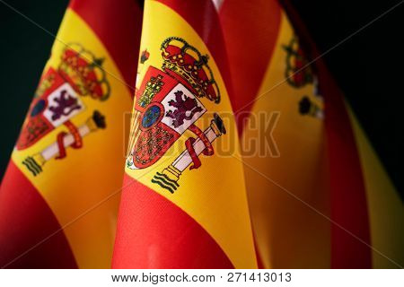 closeup of some flags of spain against a dark background