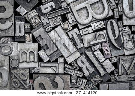 background of random vintage letterpress metal type printing blocks, black and white image
