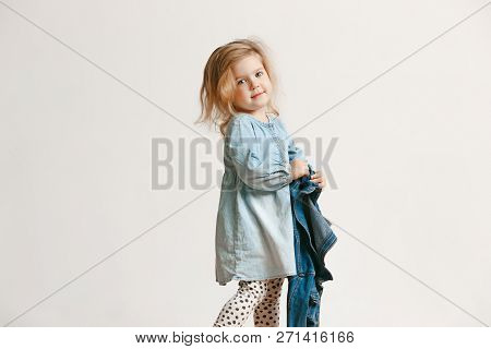 Full Length Portrait Of Cute Little Kid Girl In Stylish Jeans Clothes Looking At Camera And Smiling,