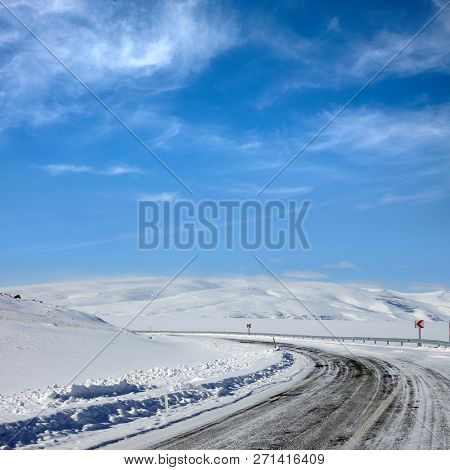 Empty frozen asphalt road and snow covered landscape with mountain over blue sky in winter time