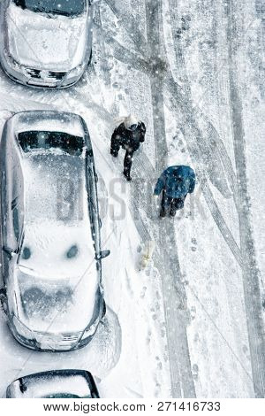 Elevated view of man and woman couple walking during snow on frozen street with covered parked cars