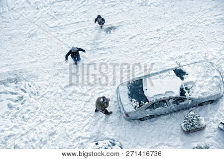Elevated view of family play in snow covered parking lot