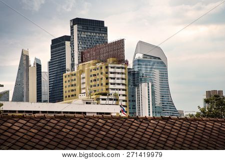 cityscape of modern architecture buildings over moody sky in downtown Bangkok, Thailand